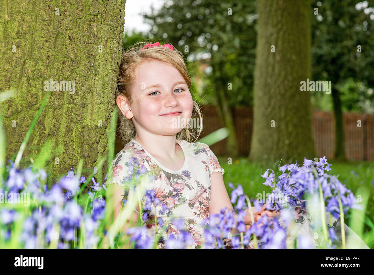 United Kingdom, UK, West Midlands, Warwickshire, Rugby, Portrait of girl (8-9) smiling among flowers - Stock Image