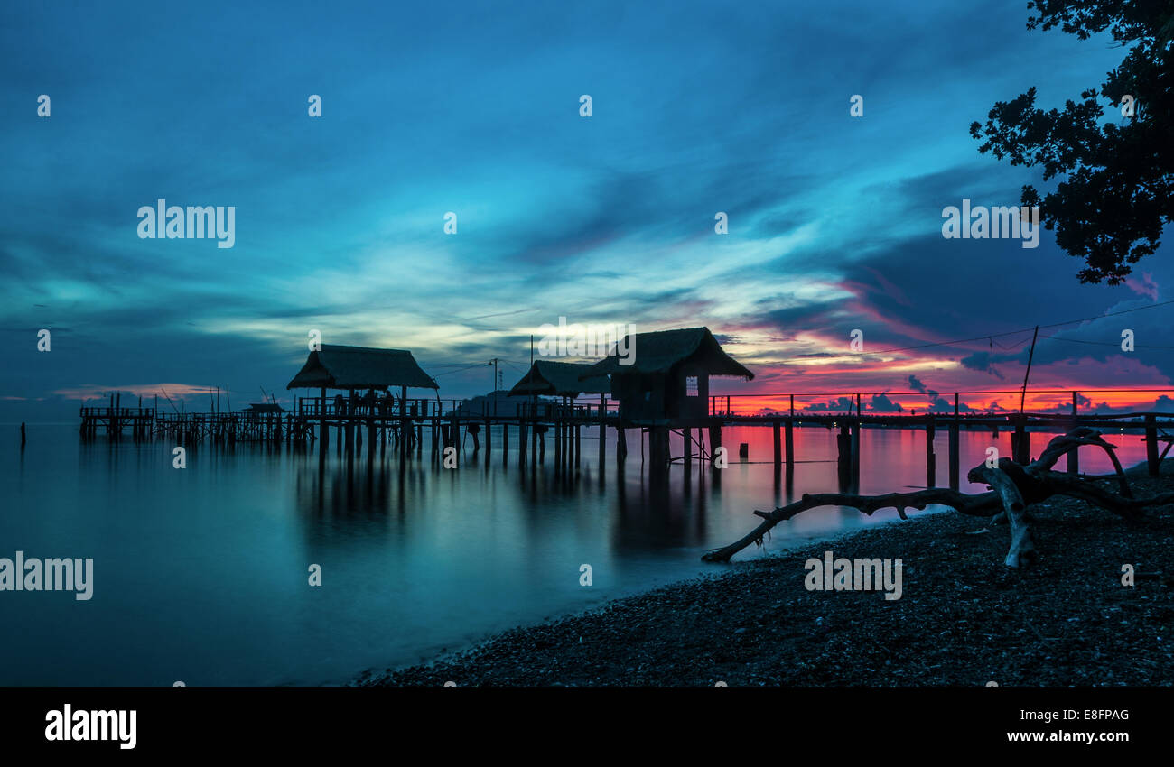 View of old fishing wharf in silhouette - Stock Image