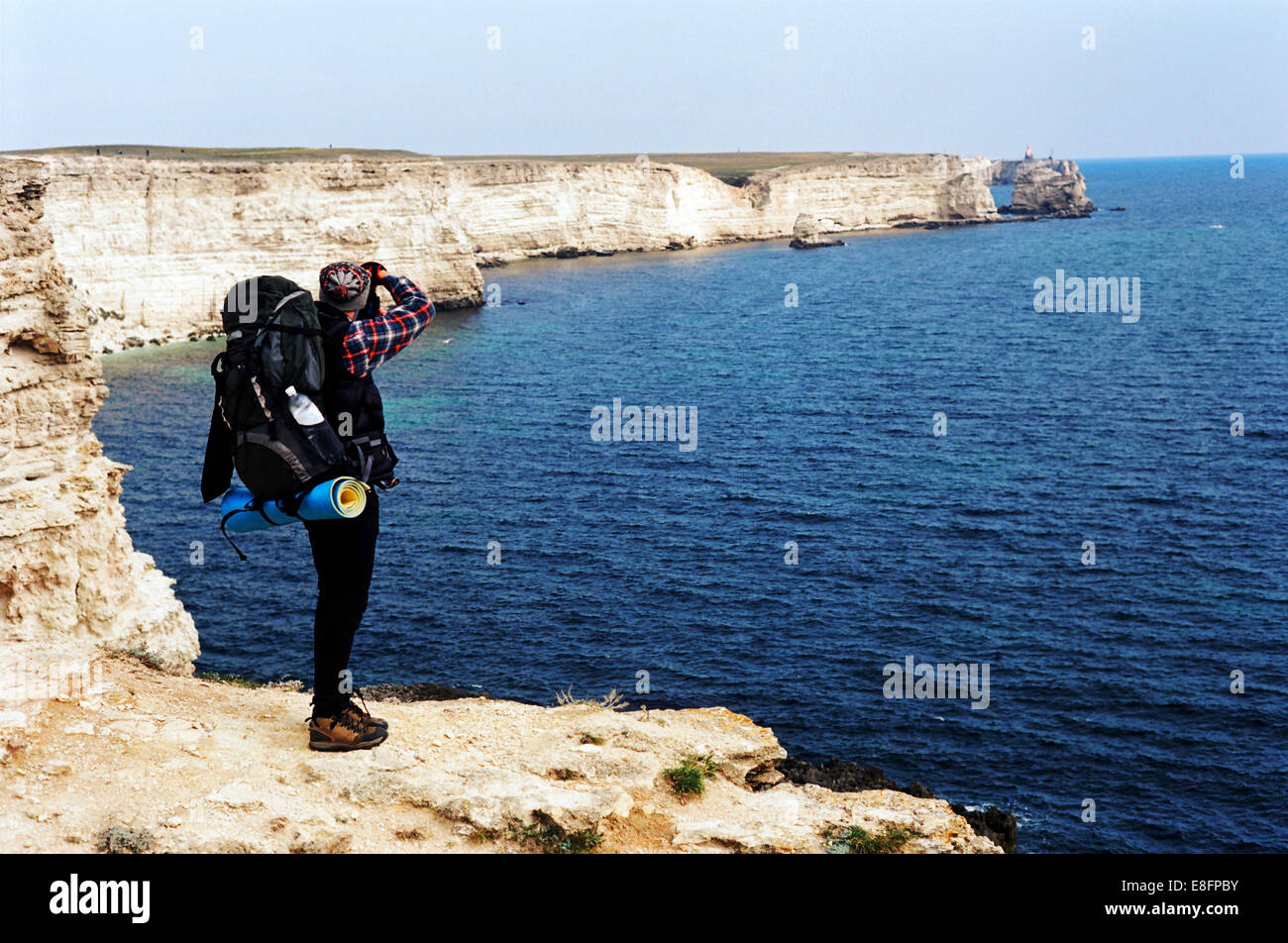 Hiker at cliff edge taking photograph of sea, rear view - Stock Image