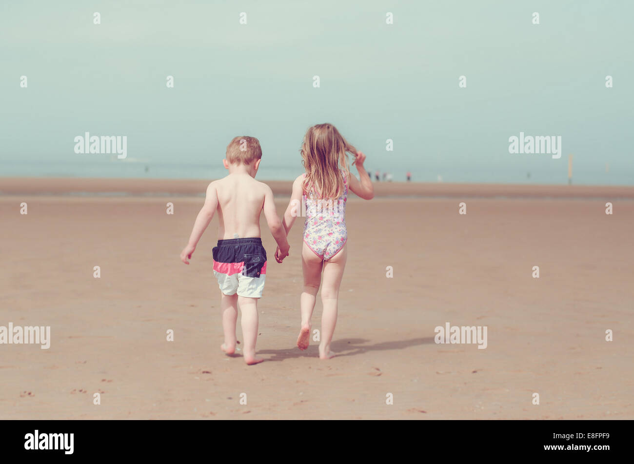 Girl and boy holding hands and walking on beach Stock Photo