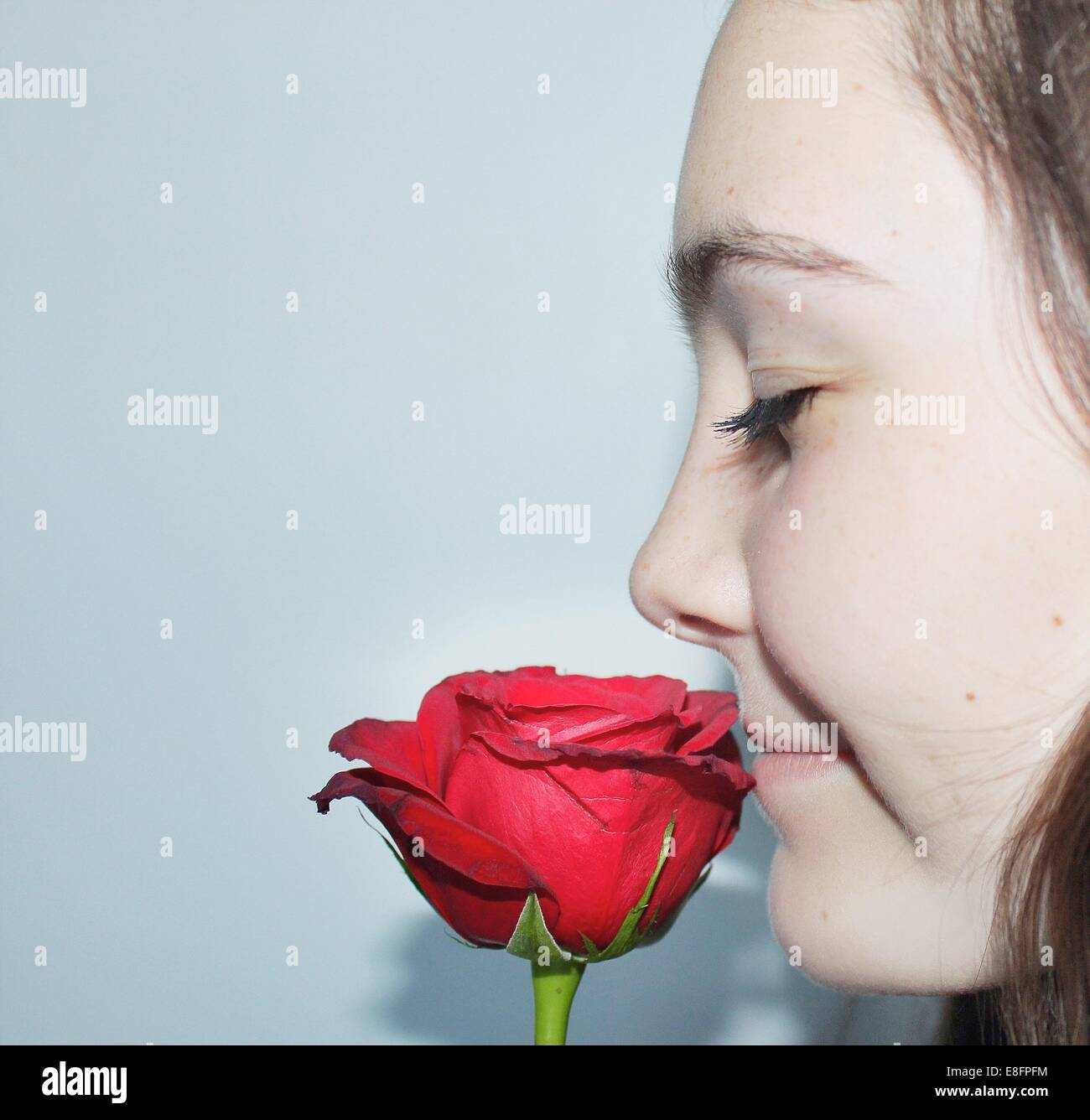 Close-up portrait of a teenage girl with eyes closed smelling a rose flower - Stock Image