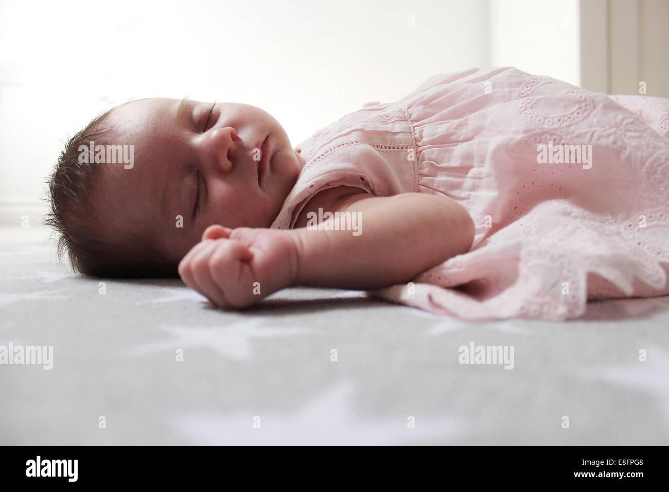 Baby girl lying on blanket sleeping - Stock Image