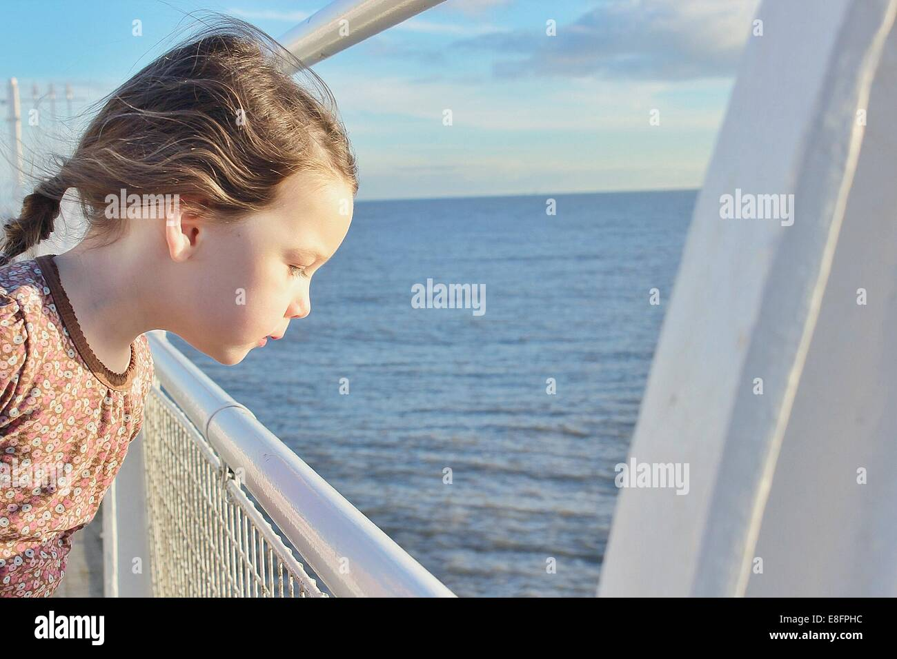 Girl standing on boat looking out to sea - Stock Image