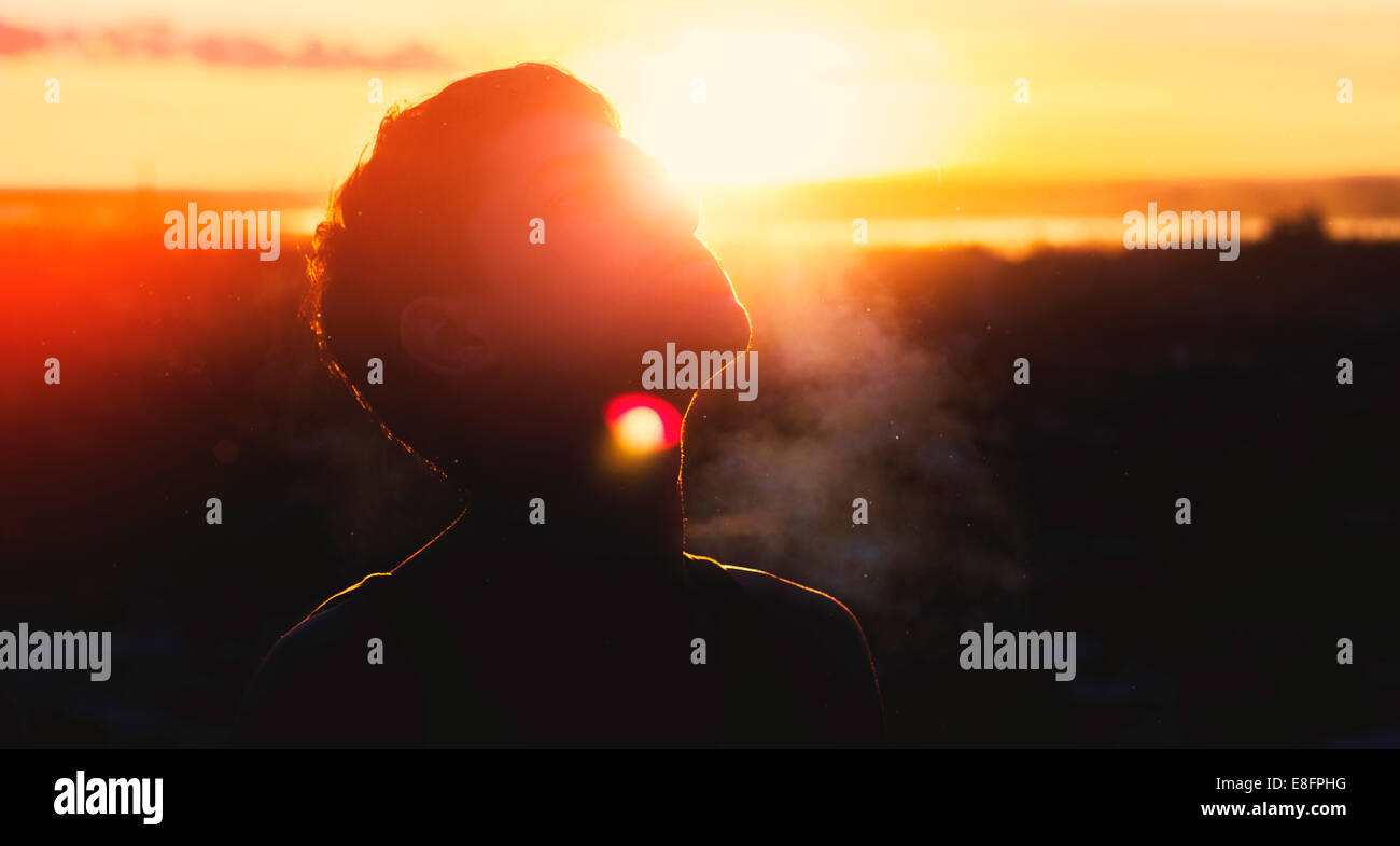 Silhouette of man at sunset - Stock Image
