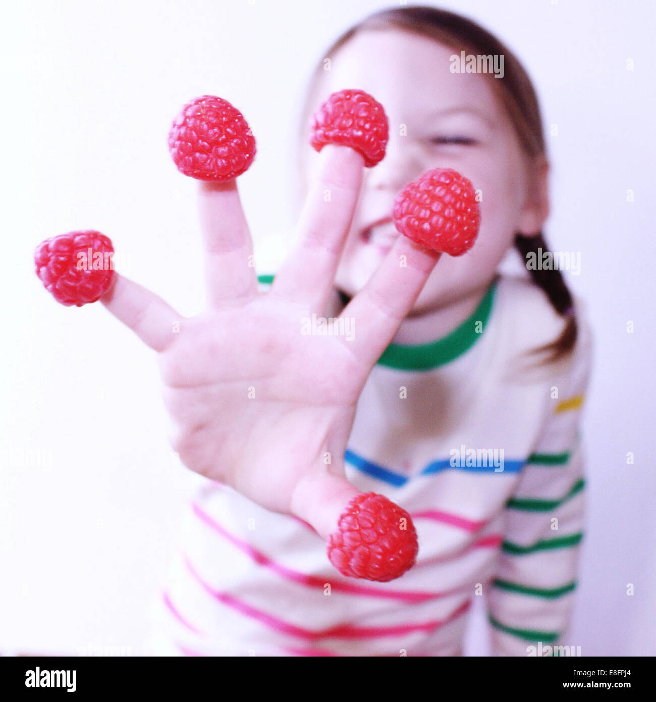 Girl with raspberries on her fingers Stock Photo