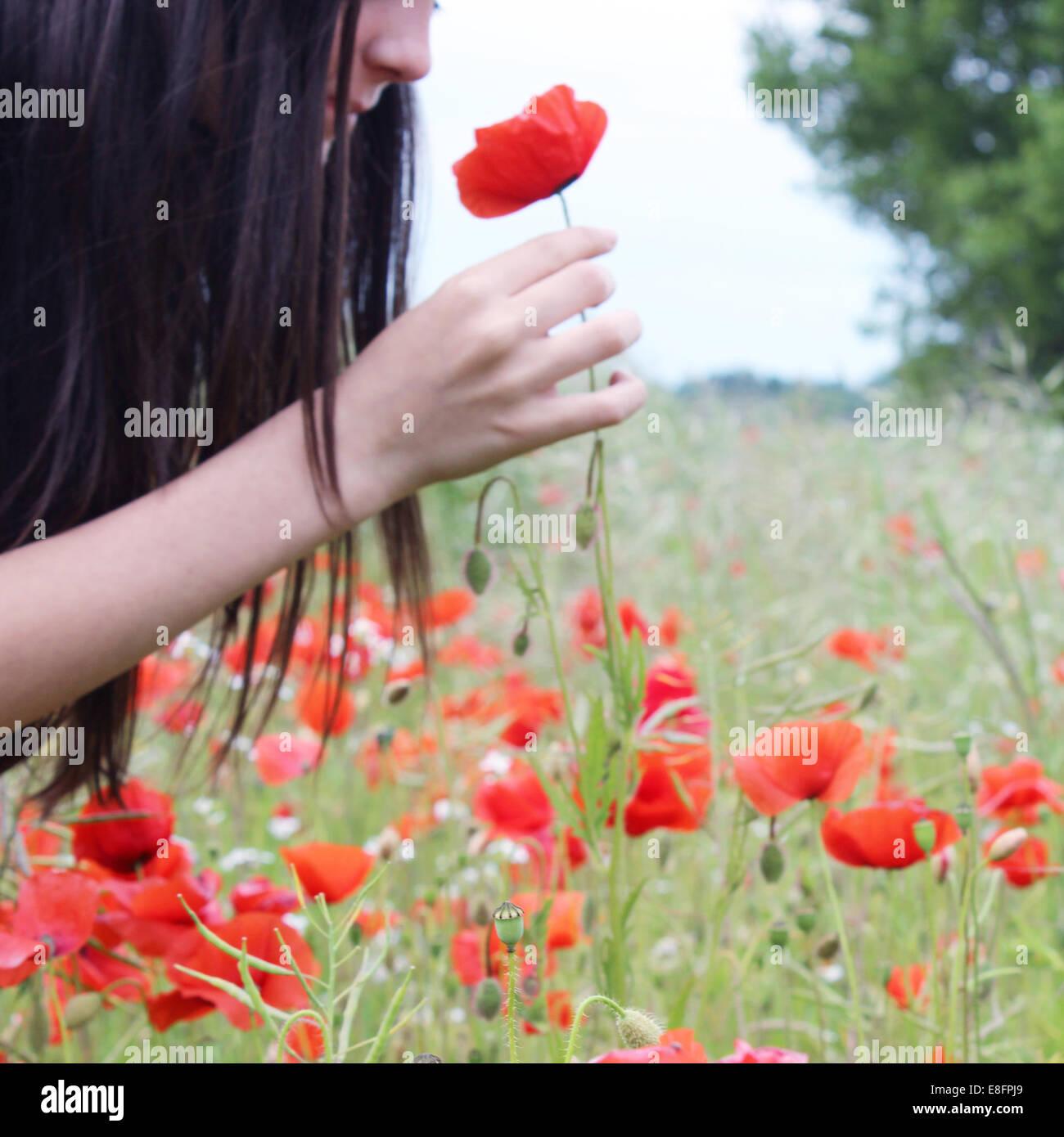 Girl smelling poppy flower Stock Photo
