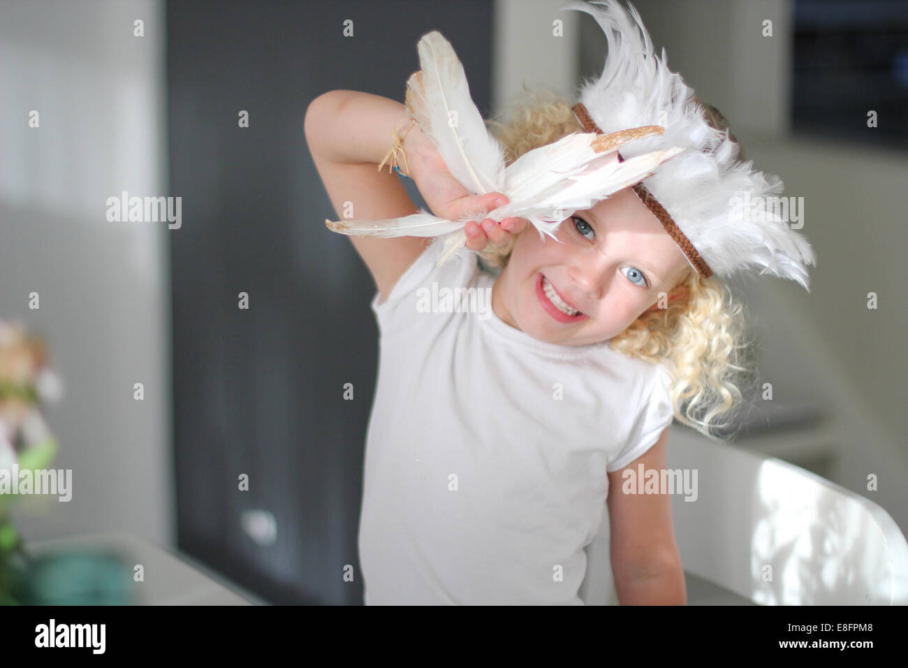 Portrait of girl wearing feather headdress holding feathers - Stock Image