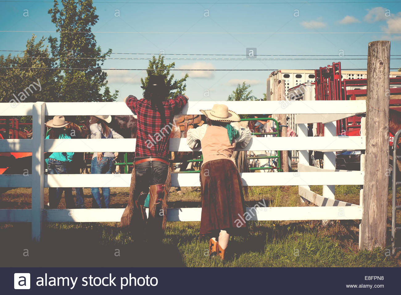 USA, Connecticut, Rear view of couple at rodeo leaning on cattle fence Stock Photo