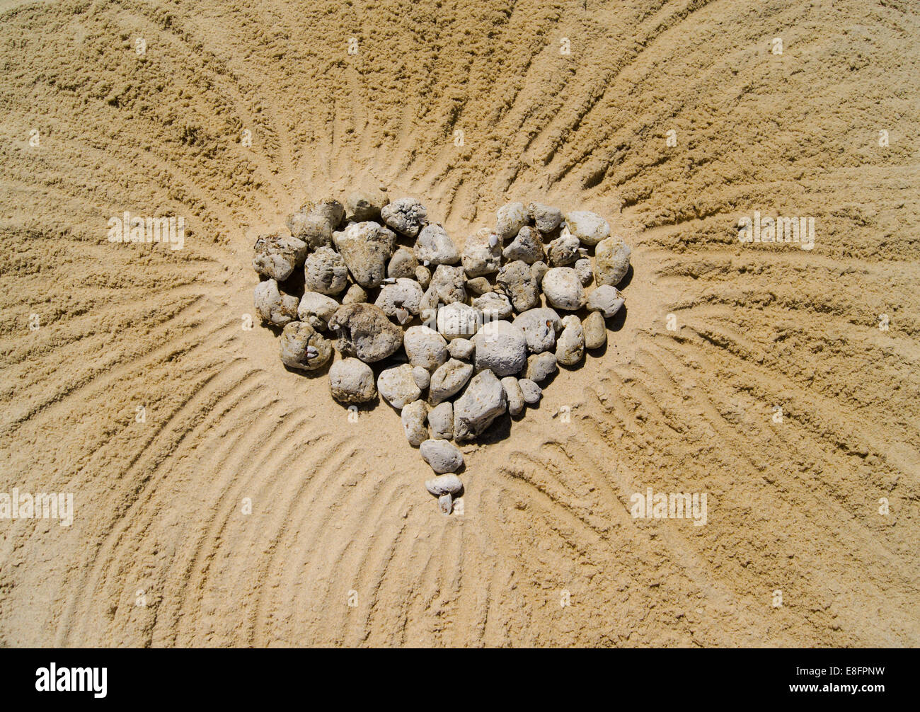 Heart made of pebbles in sand Stock Photo