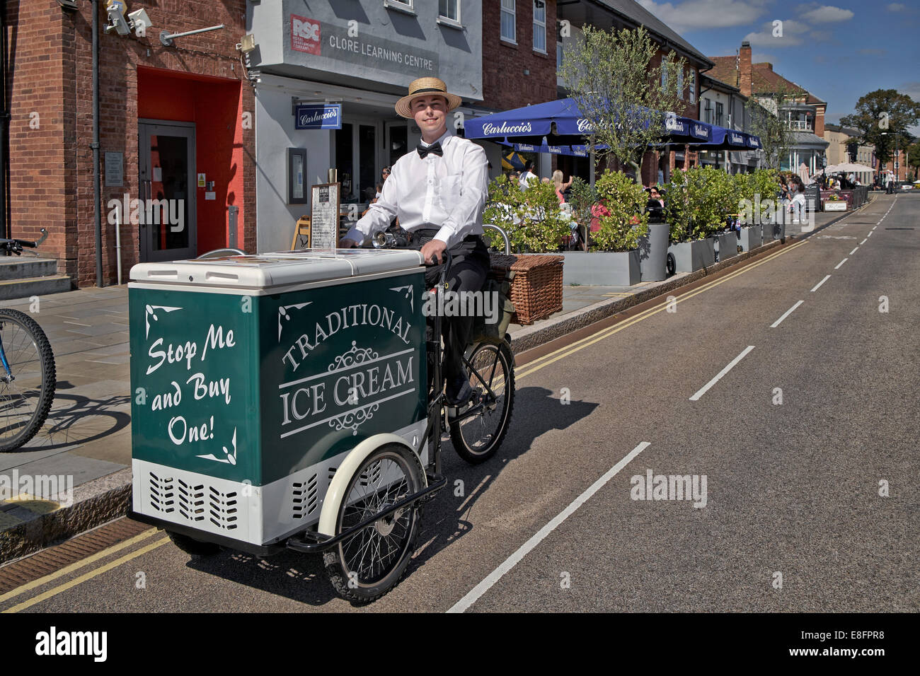 Entrepreneurial young man selling Ice cream from a vintage styled bicycle and cart in the tourist town of Stratford - Stock Image