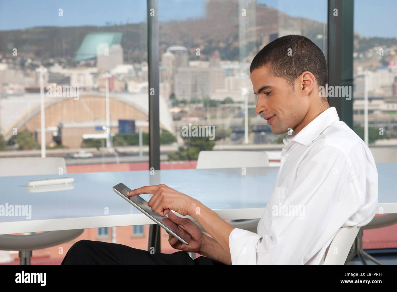 Businessman siting in an office with digital tablet - Stock Image