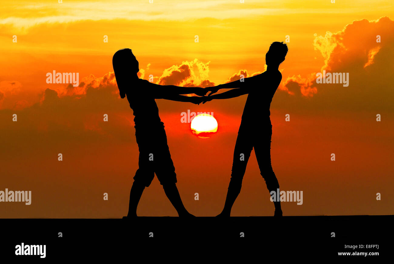 Silhouette of a Couple holding hands on beach at sunset, Thailand - Stock Image