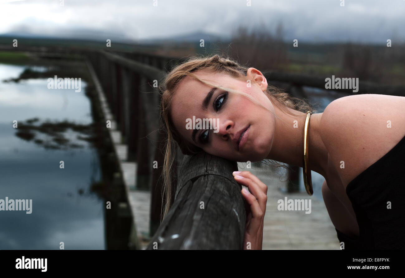 Fashion model leaning on railing of bridge Stock Photo