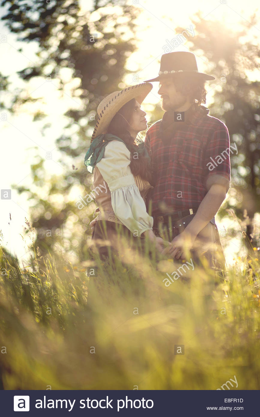 Cowboy and cowgirl couple in field - Stock Image