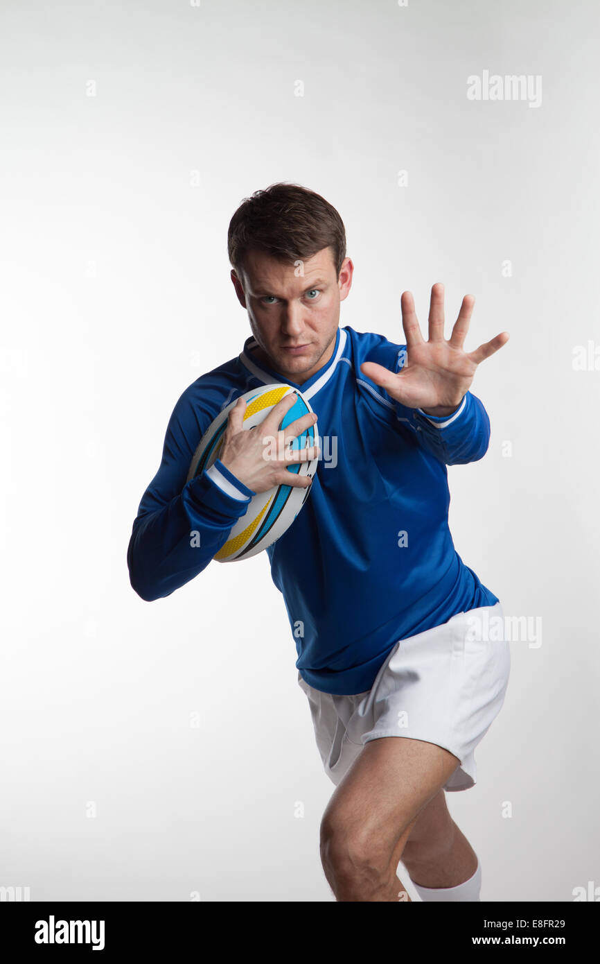 Rugby player running with rugby ball Stock Photo