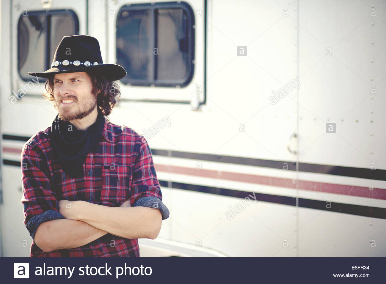 Portrait of modern day cowboy standing by trailer - Stock Image