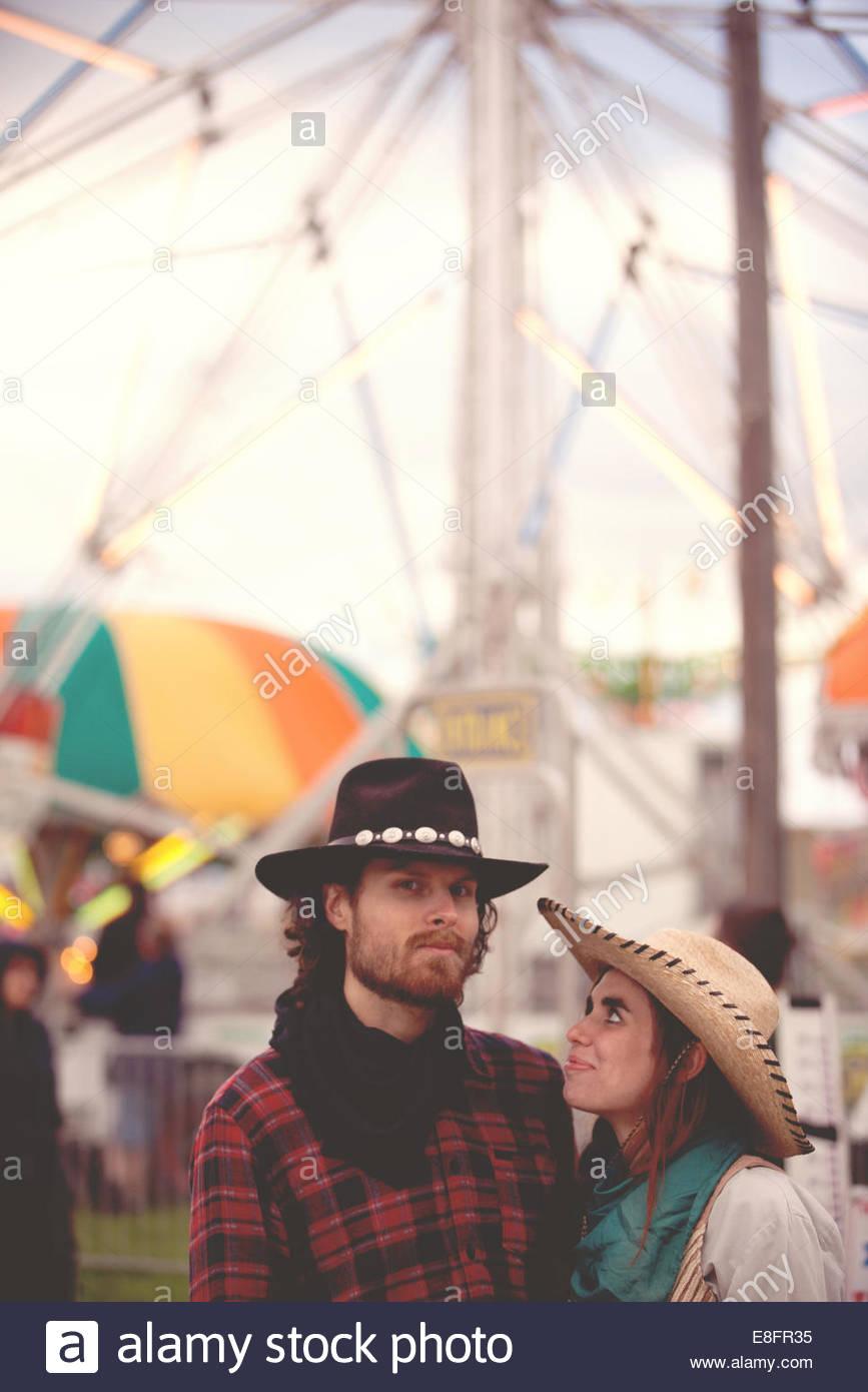 Portrait of couple wearing cowboy hats at fairground - Stock Image