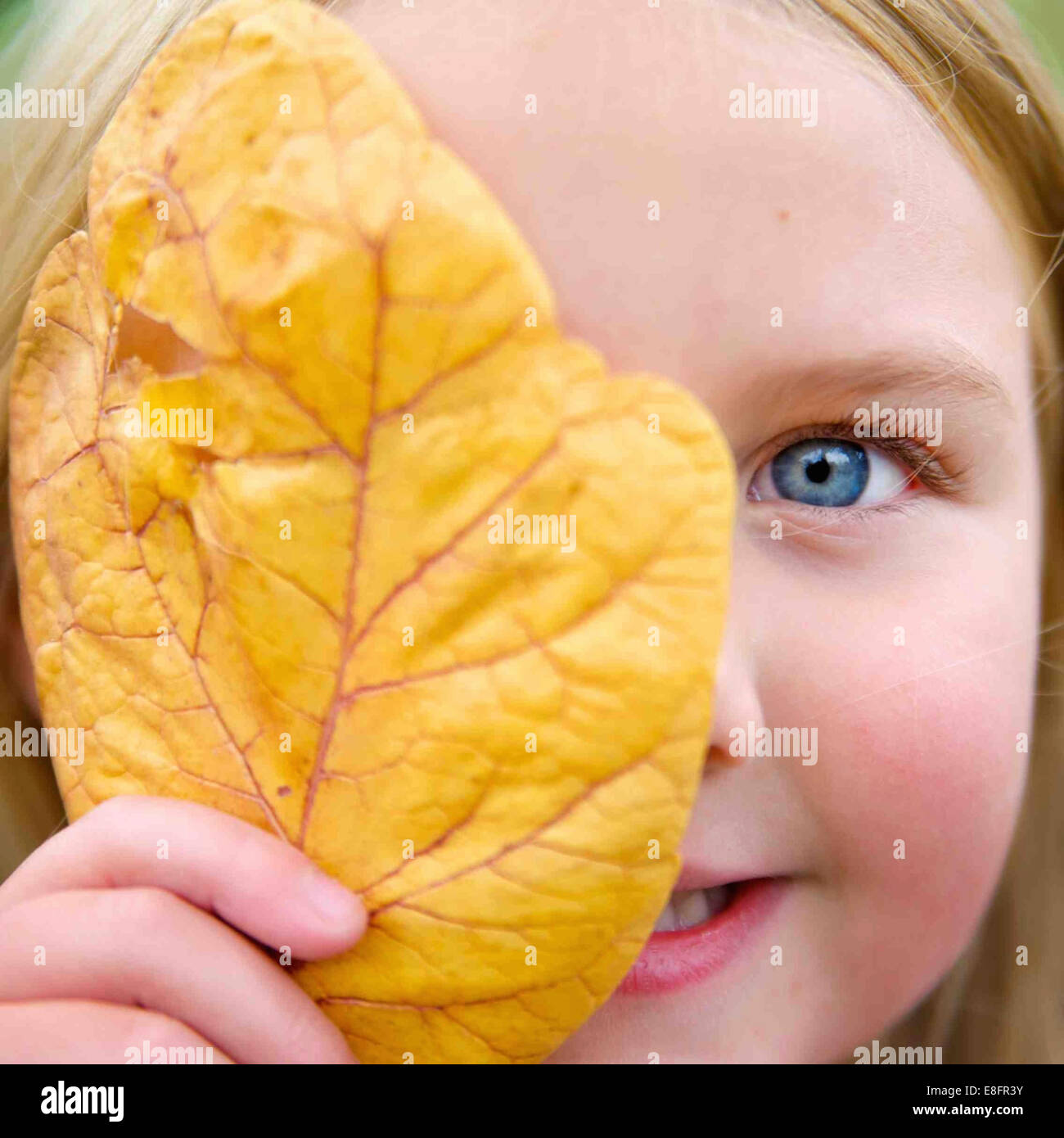 Portrait of a girl holding a leaf in front of her face - Stock Image