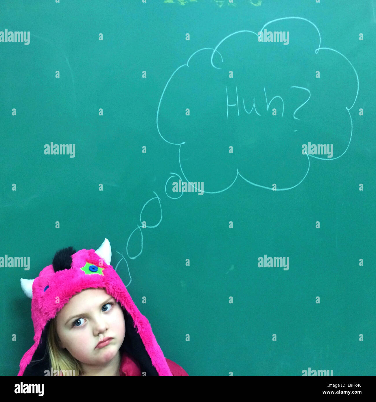 Portrait of a Girl standing in front of blackboard with puzzled expression - Stock Image