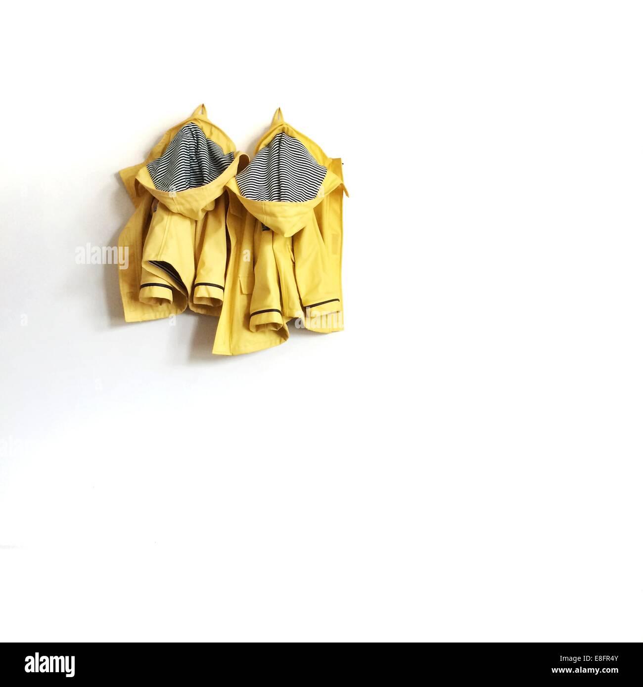 Two yellow raincoats hanging on wall - Stock Image