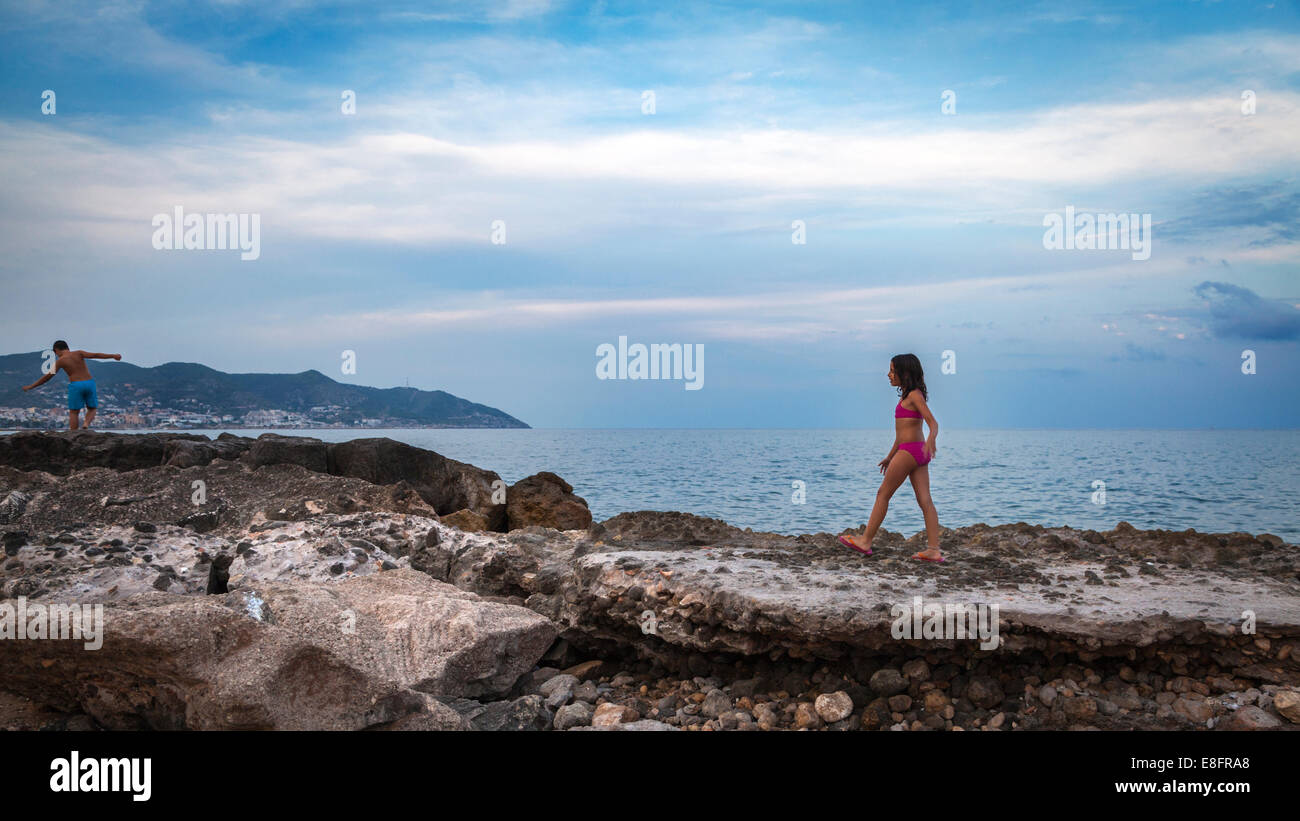 Two children walking along rocky beach, Barcelona, Spain - Stock Image