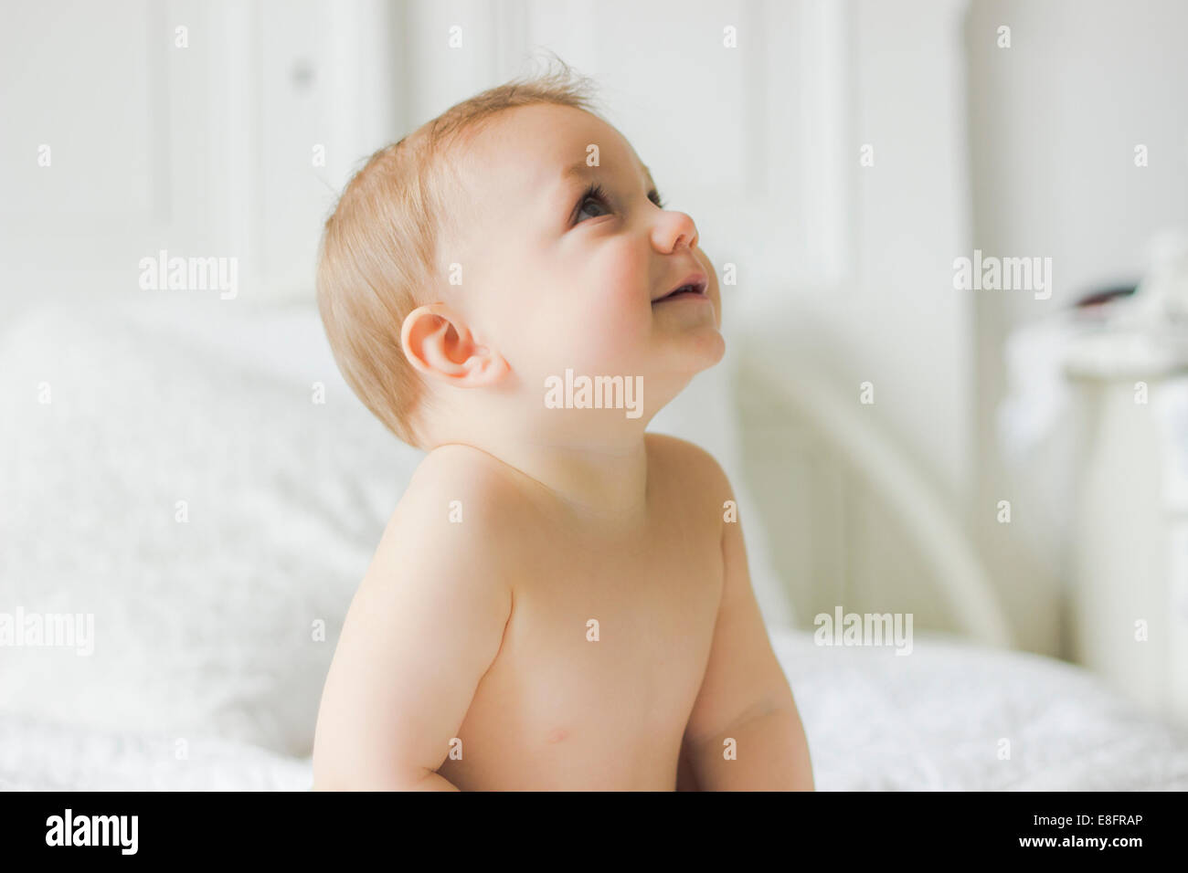 Portrait of Smiling baby sitting on bed in bedroom - Stock Image