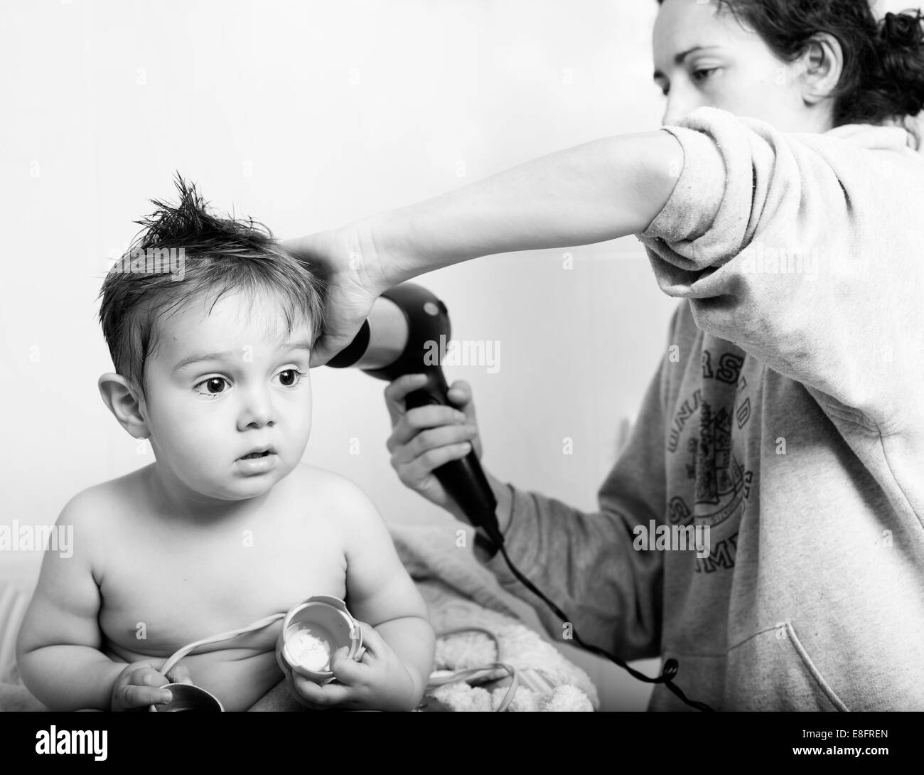 Mother blow drying her son's wet hair - Stock Image