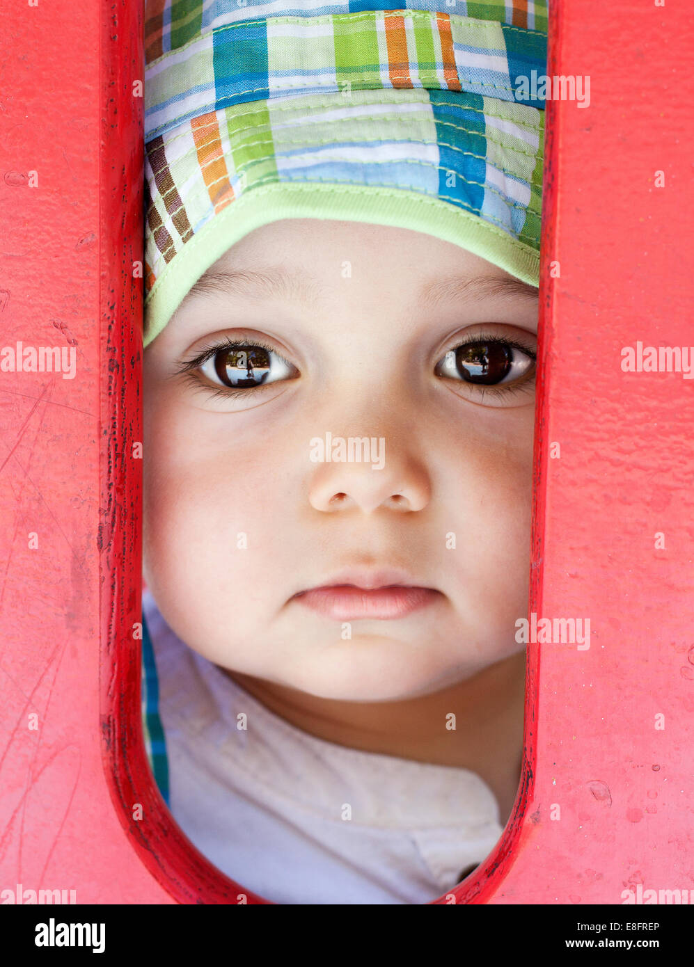 Portrait of a girl looking through railings - Stock Image