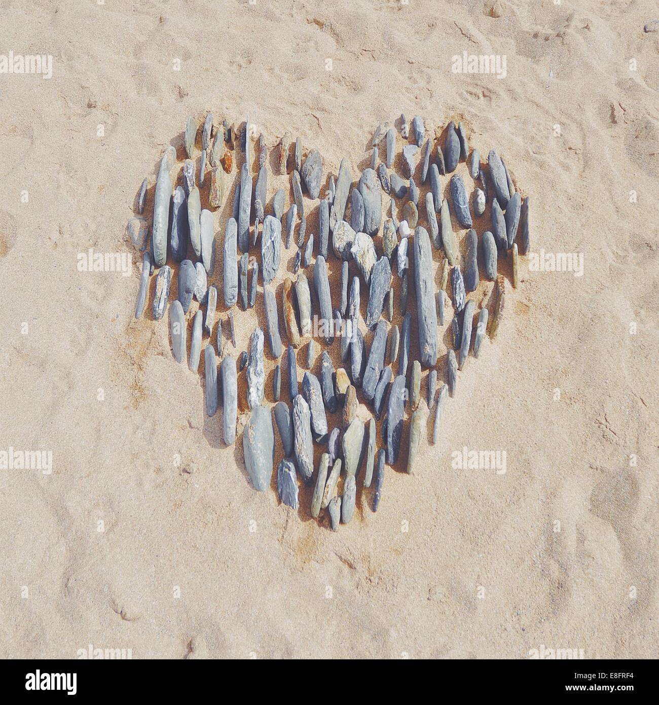 Heart in the sand made with pebbles - Stock Image