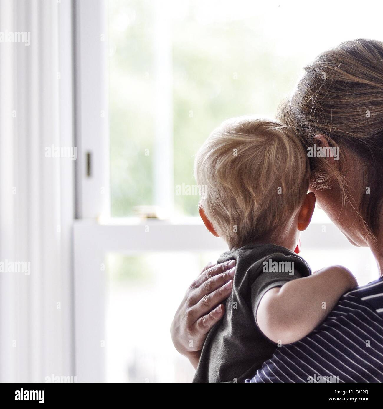 Mother and son looking out of the window - Stock Image