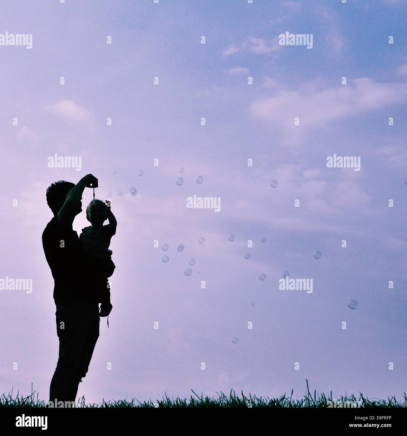 Silhouette of man and child blowing bubbles - Stock Image