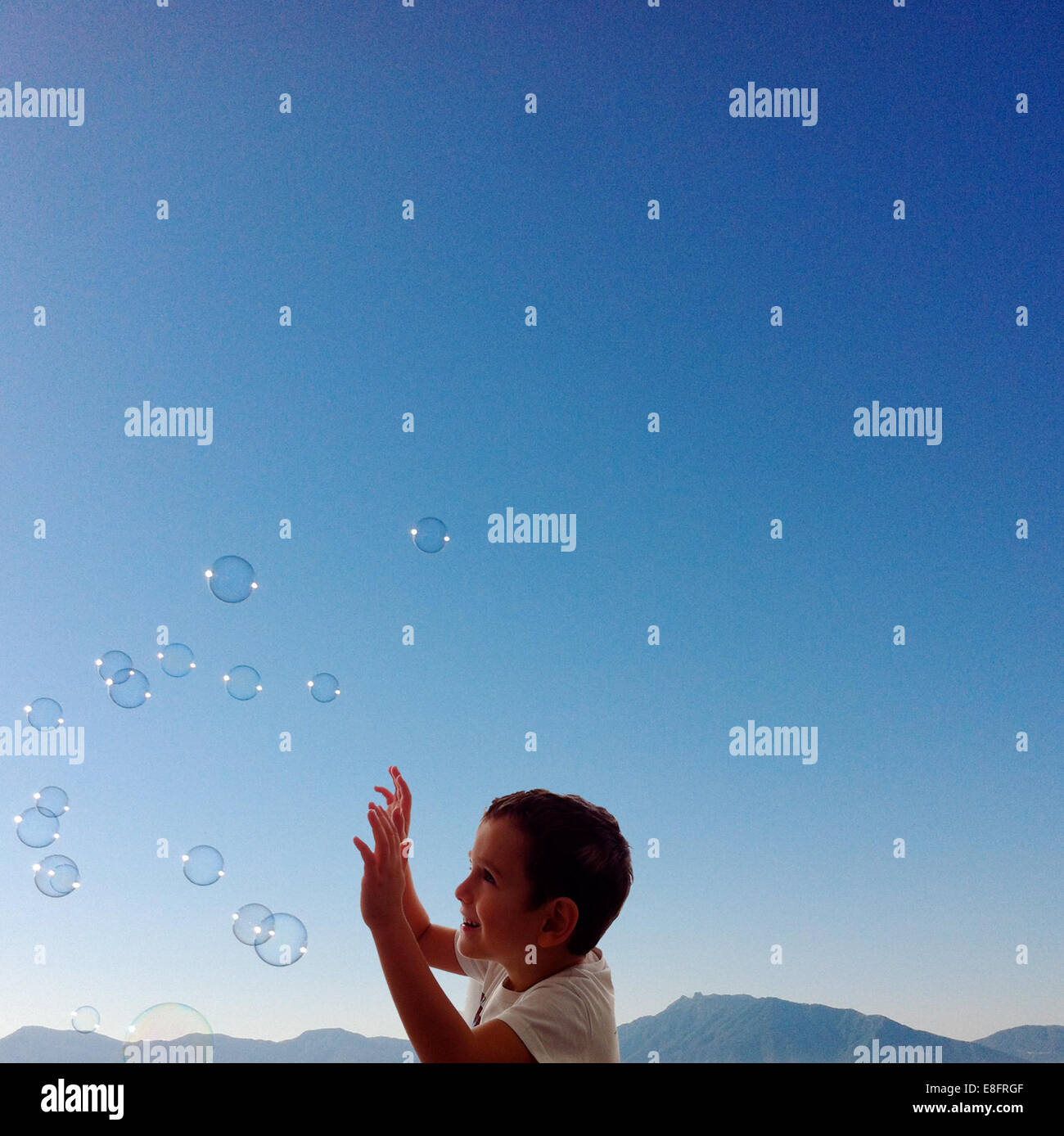 Boy (4-5) playing with bubbles - Stock Image