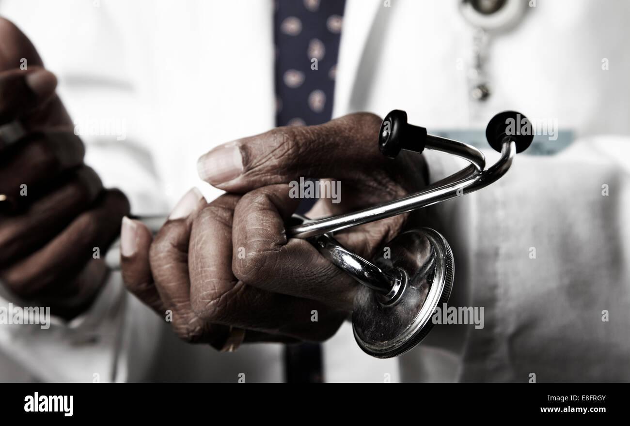 Doctor holding stethoscope - Stock Image