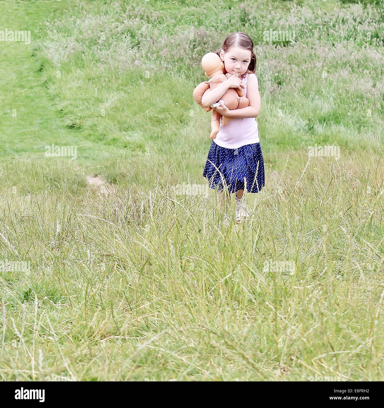 Girl walking through field carrying her doll Stock Photo