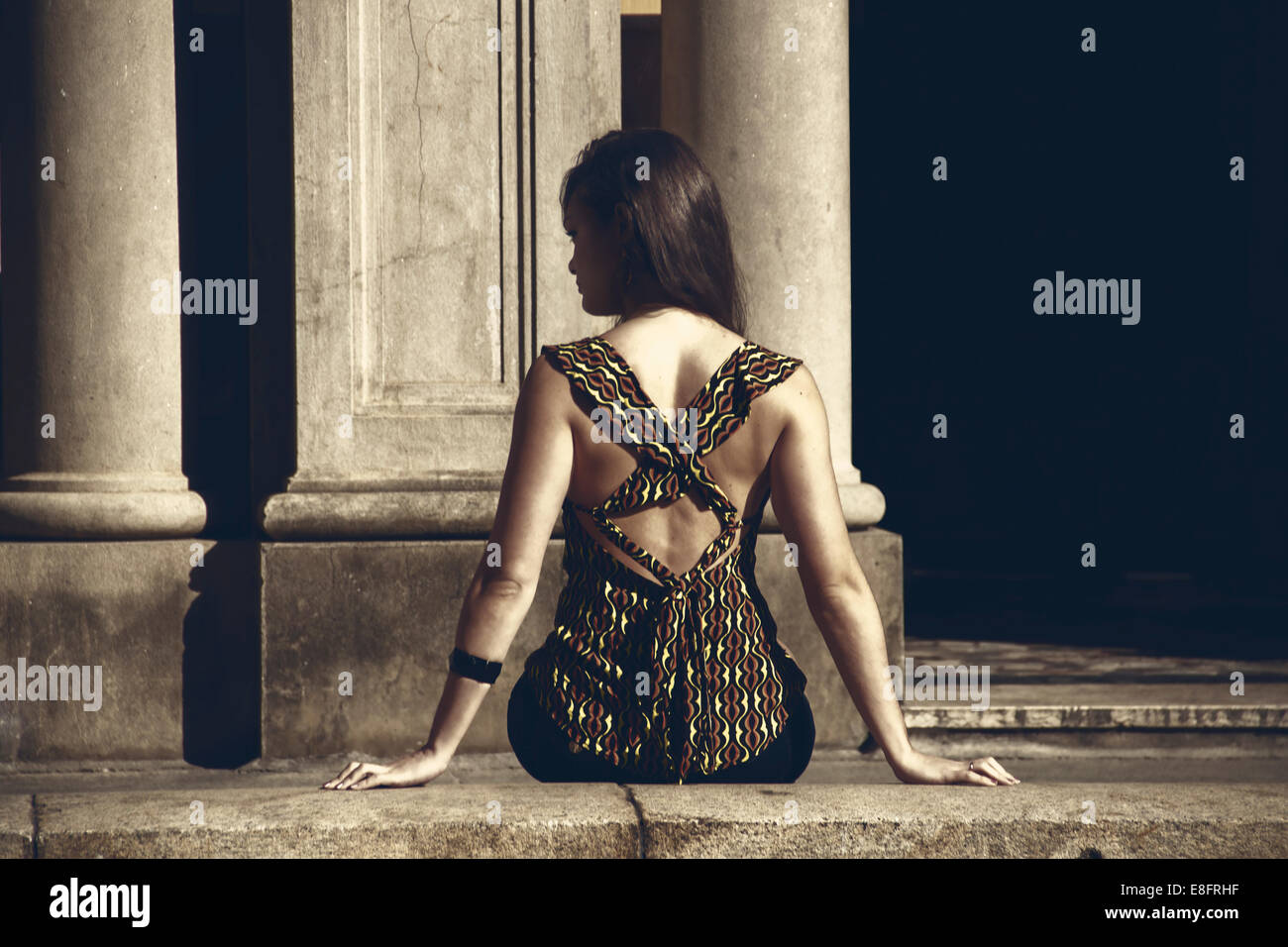 Rear view of woman sitting on a wall - Stock Image