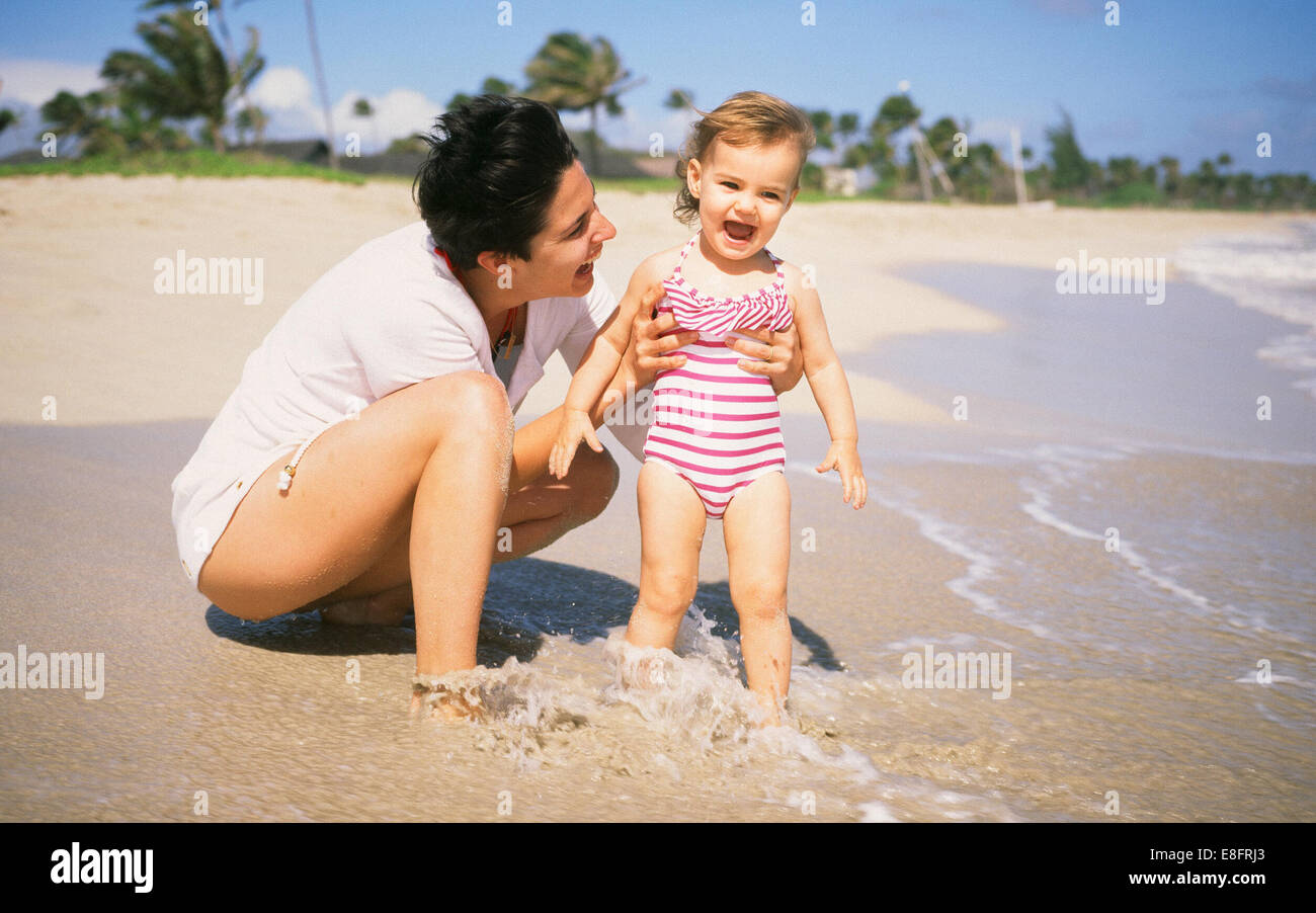 Mother and her baby daughter (18-23 months) relaxing on beach - Stock Image