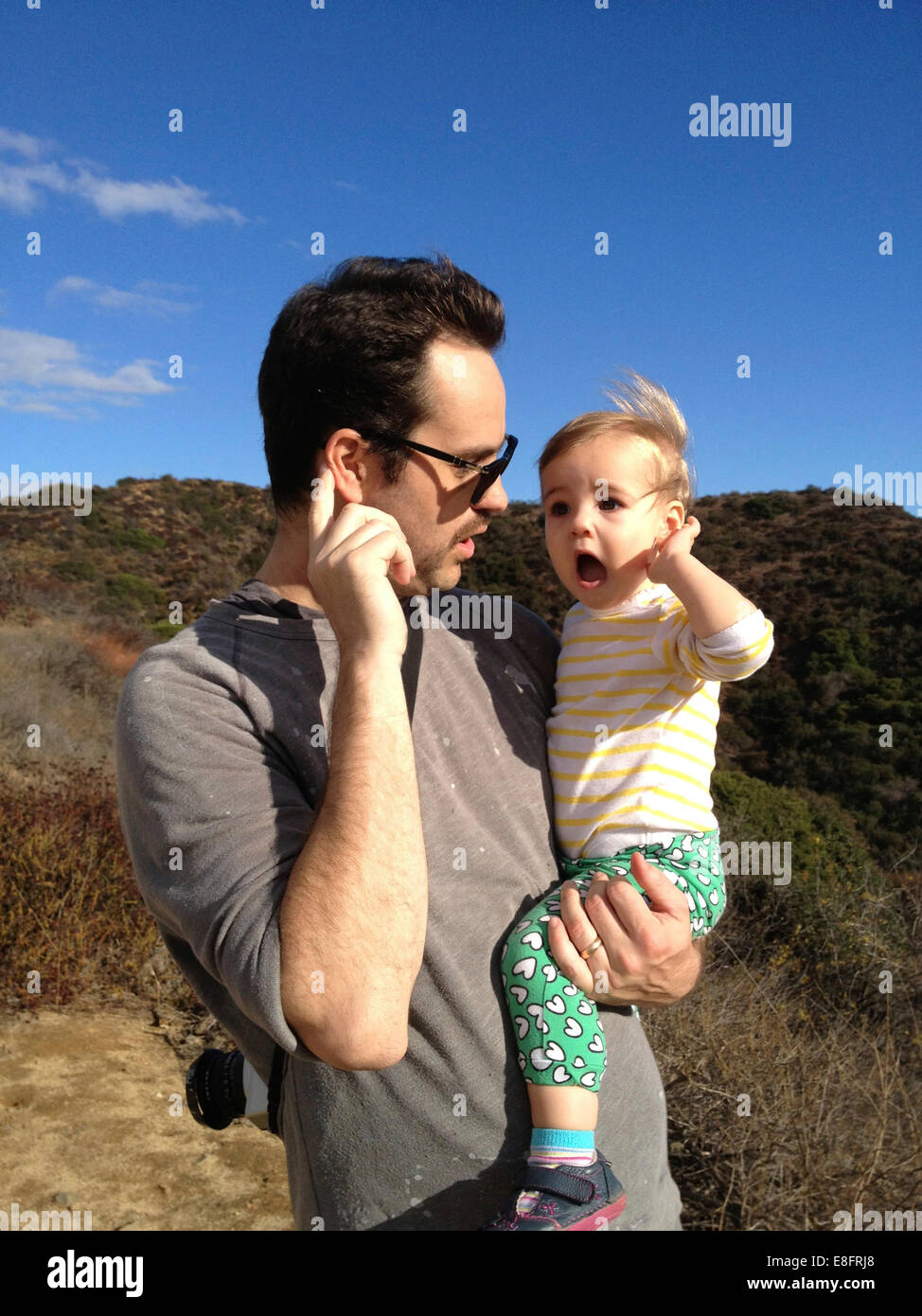 Father and daughter (18-23 months) holding hands to ears listening - Stock Image