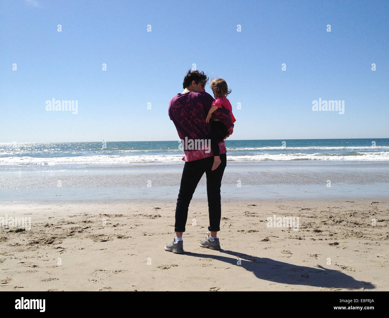 Rear view of mother holding her daughter (18-23 months) on the beach and looking at sea - Stock Image