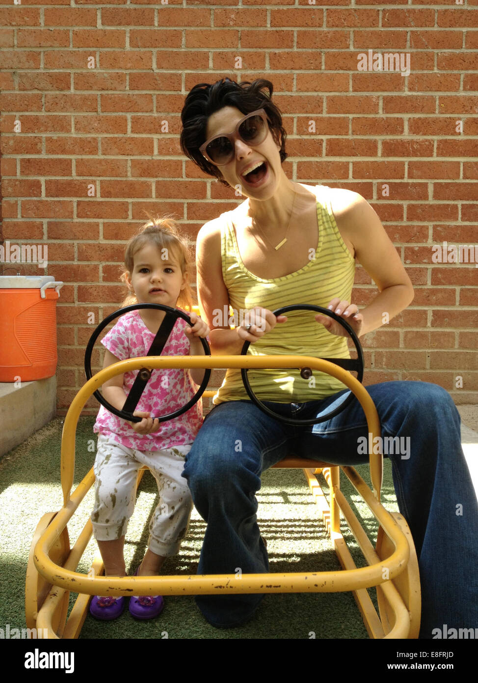 Mother and daughter (18-23 months) driving cart - Stock Image