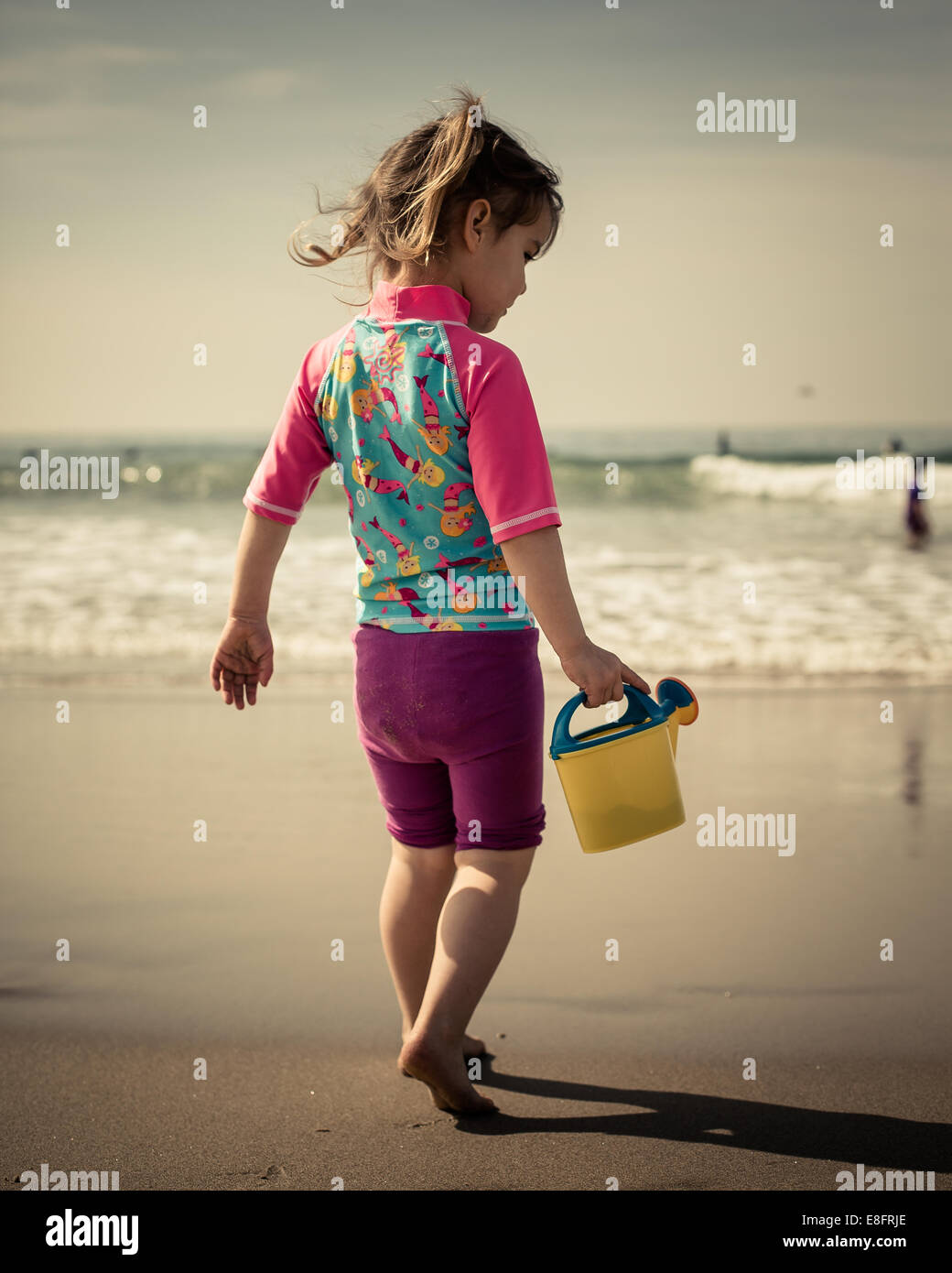 View of girl (18-23 months) walking along beach - Stock Image