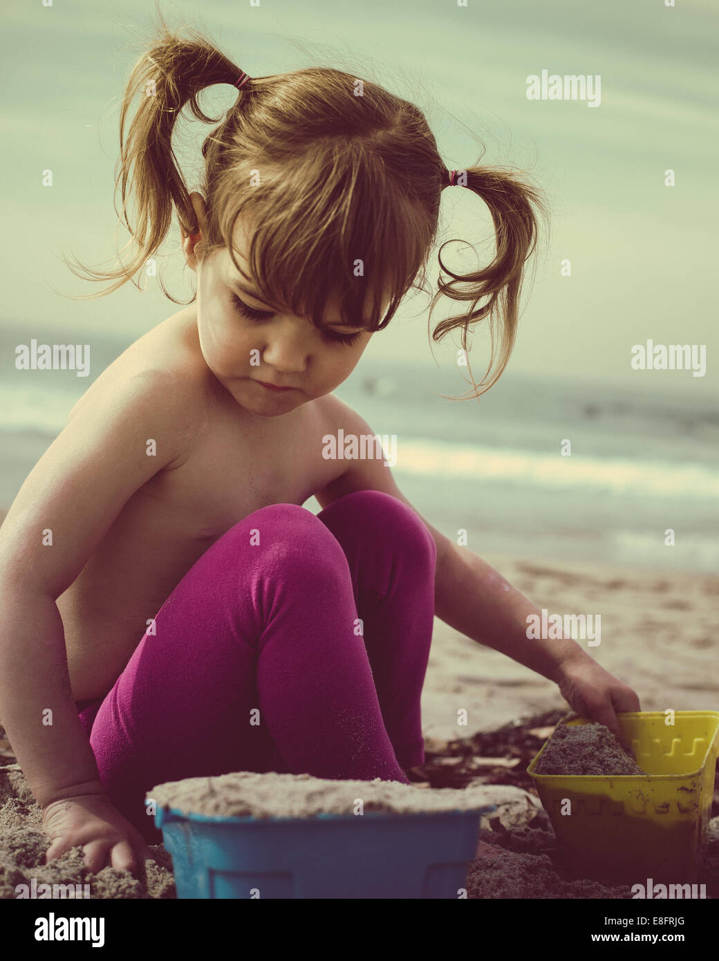 Girl (18-23 months) building sand castle on beach - Stock Image