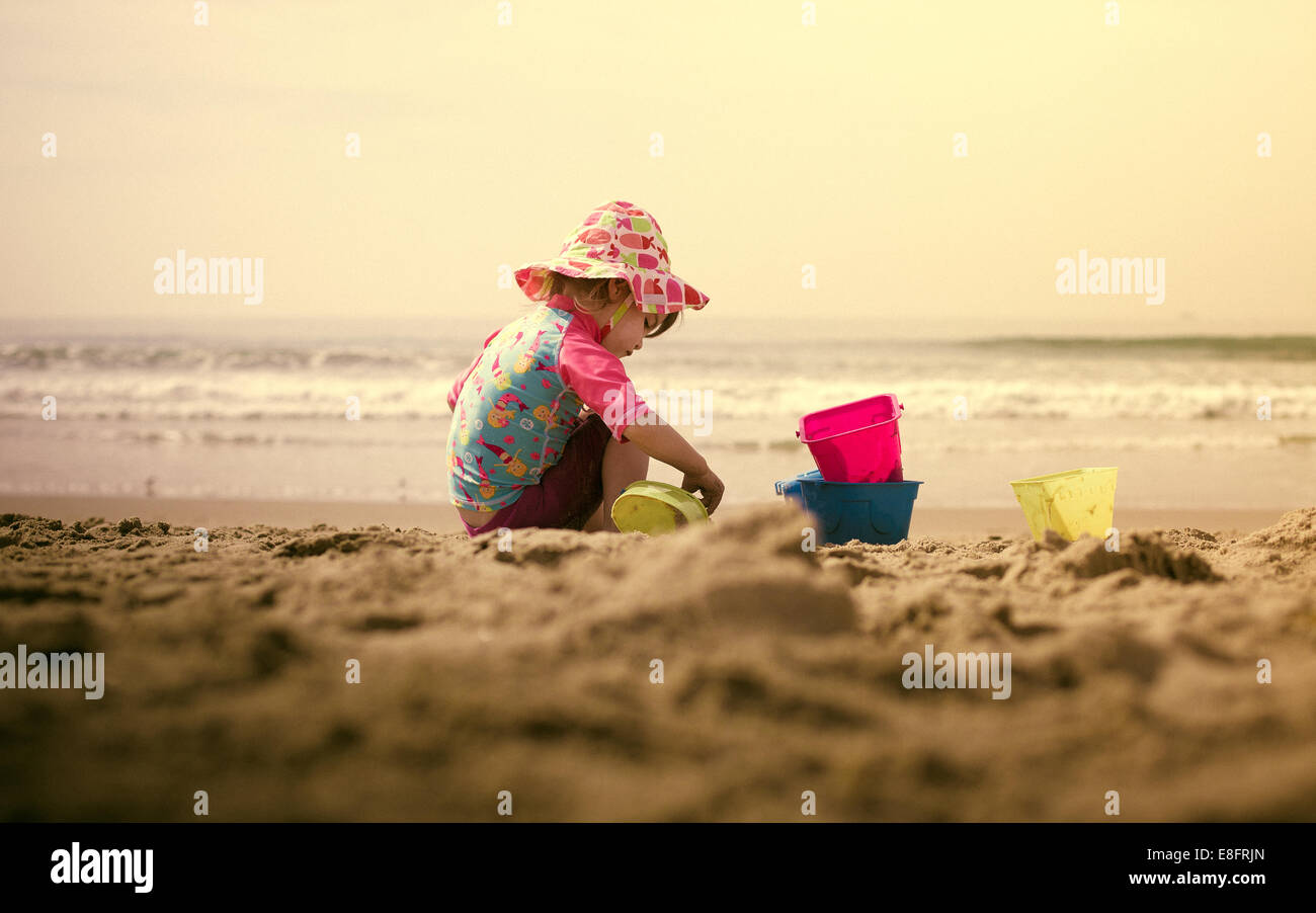 Girl (18-23 months) playing in sand on beach - Stock Image
