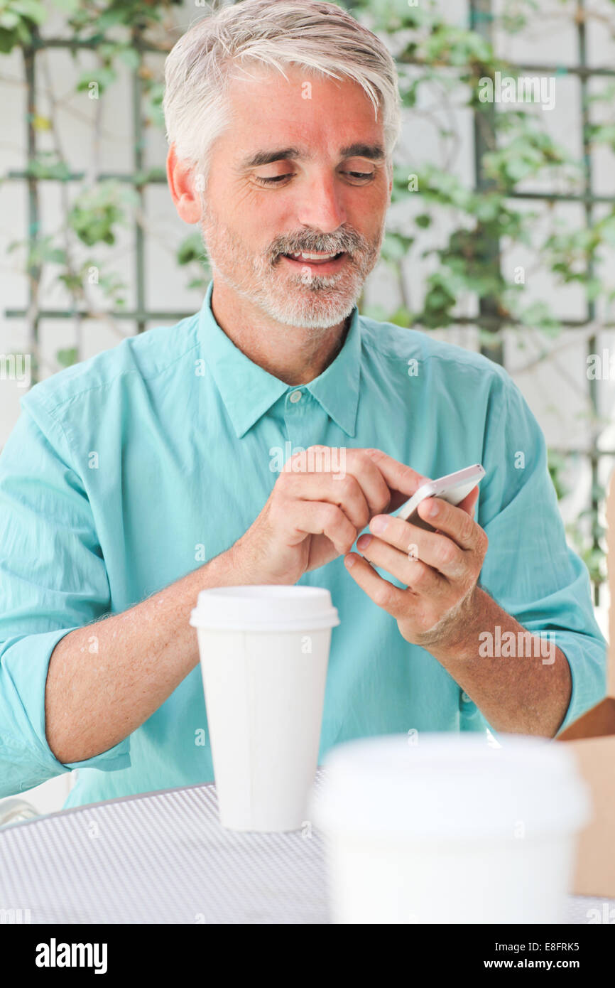 Businessman making call in sidewalk cafe - Stock Image