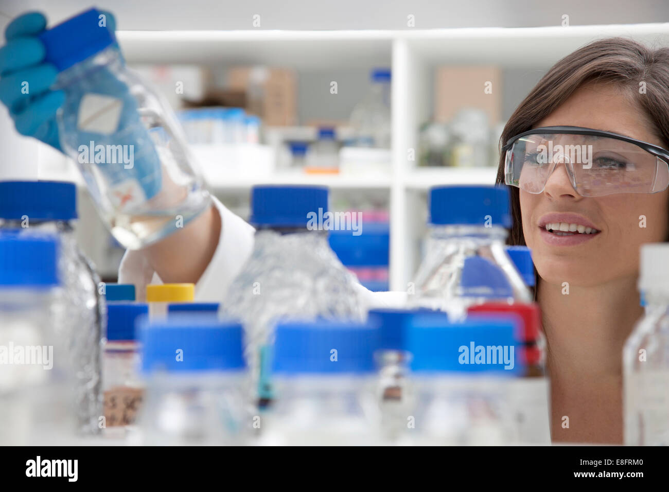 Laboratory technician looking through glass containers - Stock Image