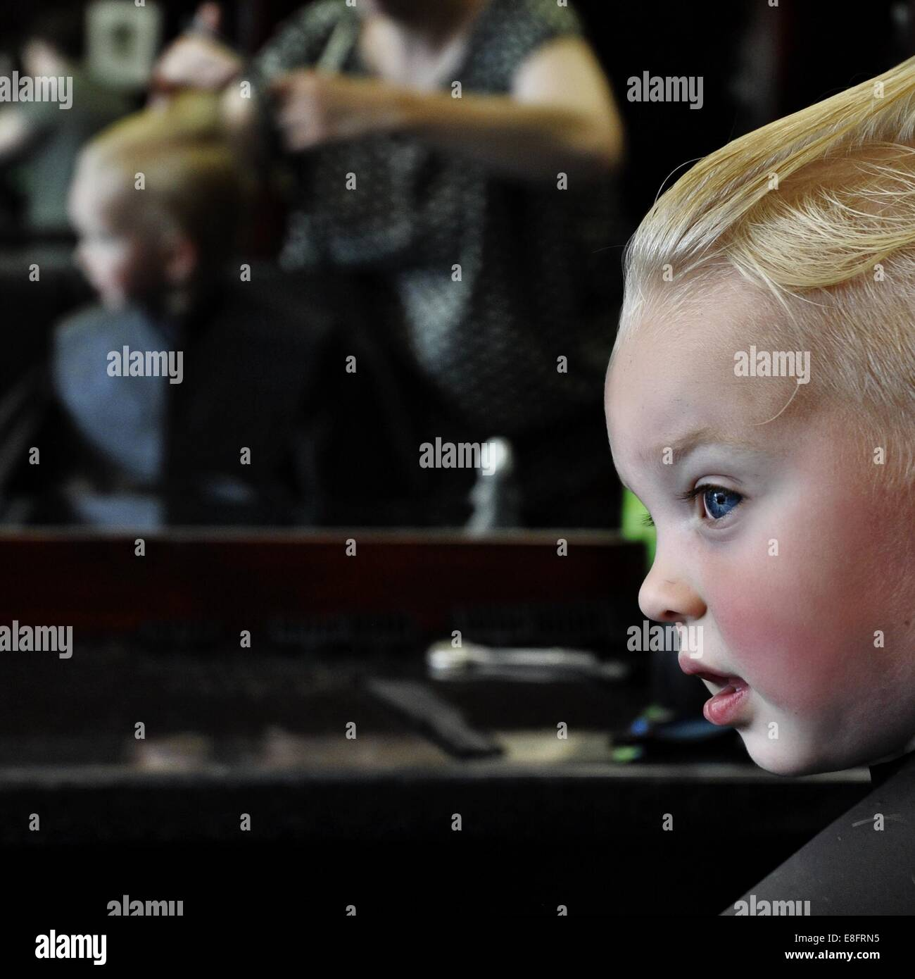 Boy having hair cut at hairdressers - Stock Image