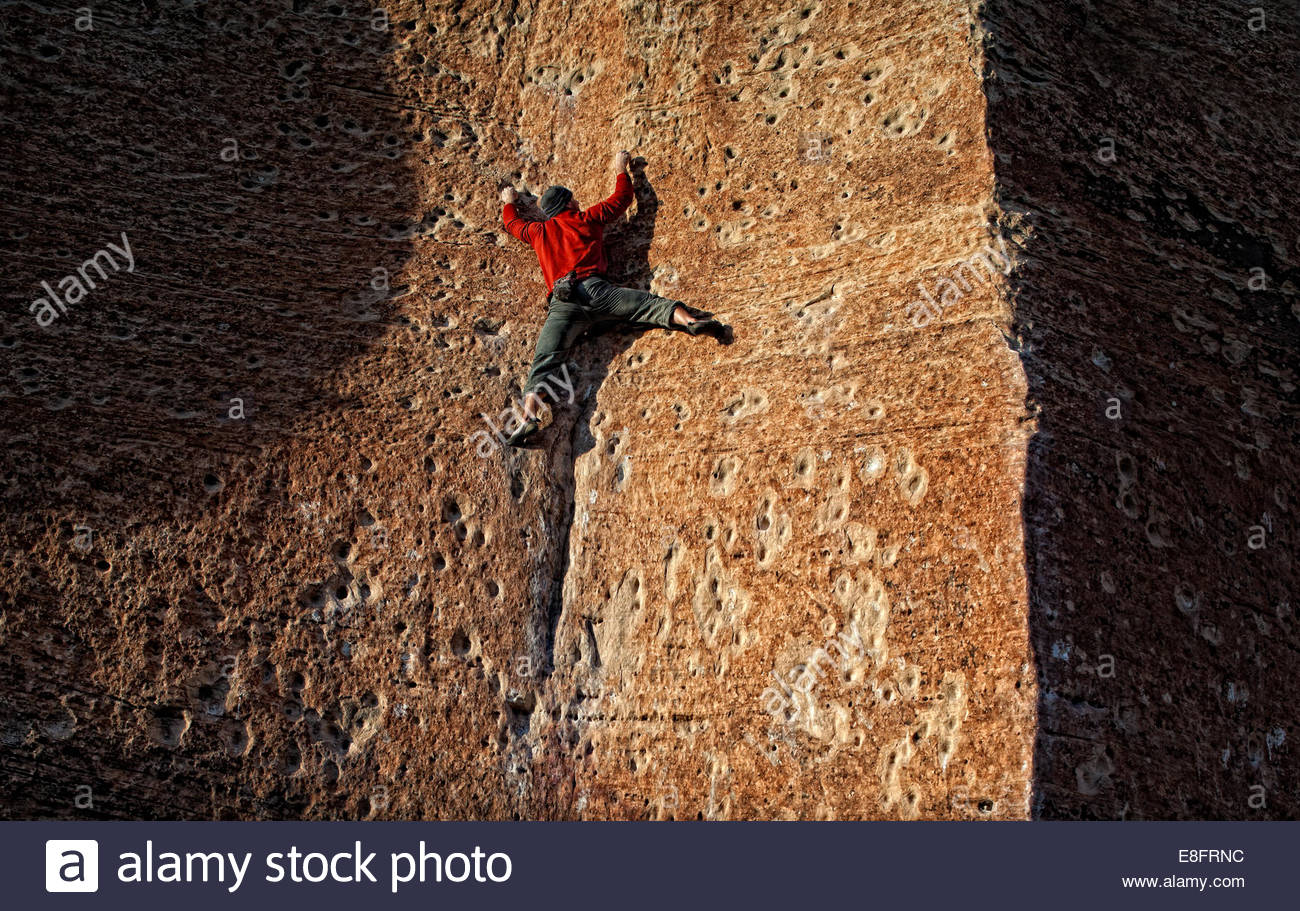 Rock climber works a sandstone slab with no rope or protection - Stock Image