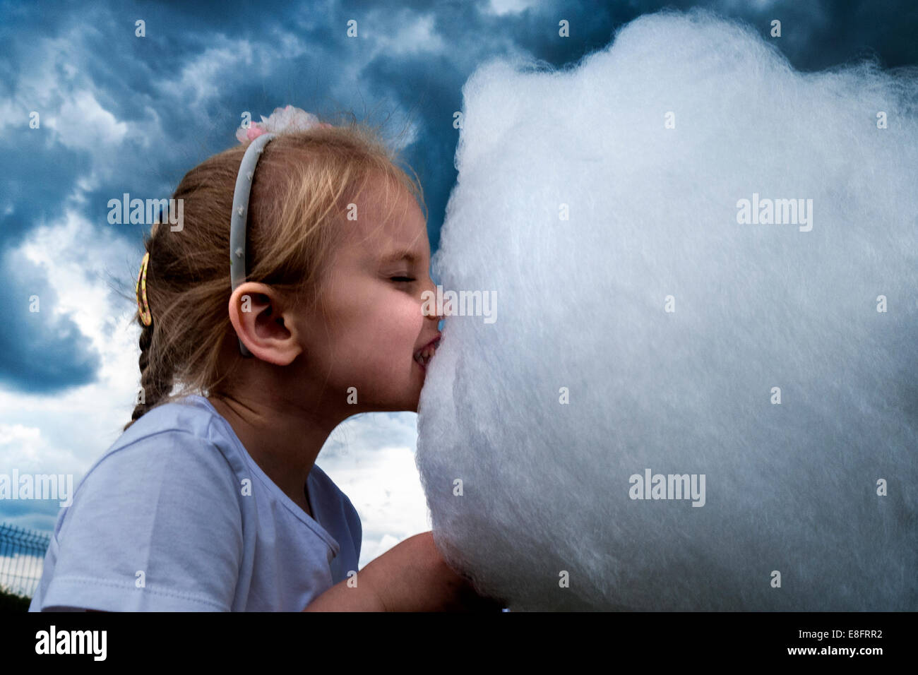 Little girl eating cotton candy with dramatic sky behind her - Stock Image