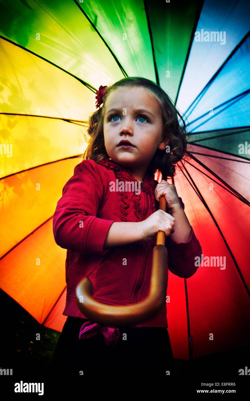 Girl (4-5) holding rainbow umbrella - Stock Image