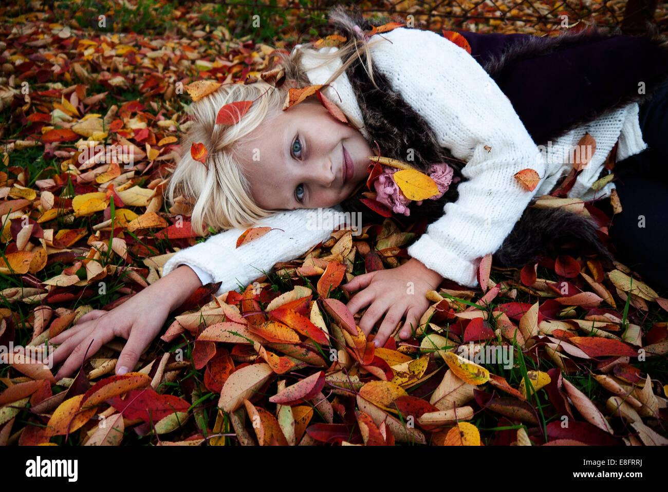 Girl (6-7) lying on autumn leaves - Stock Image