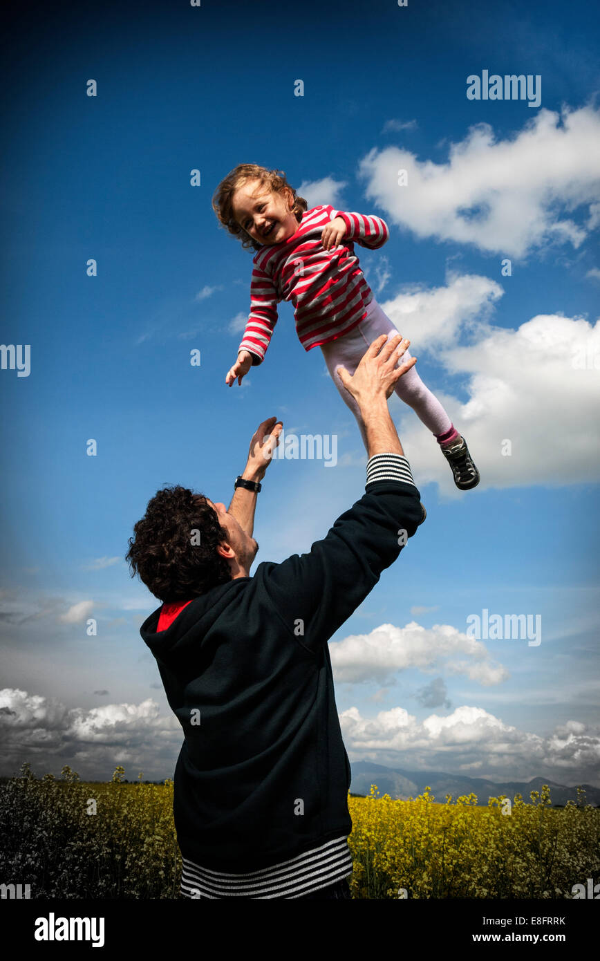 Father tossing his daughter (4-5) in flower meadow - Stock Image